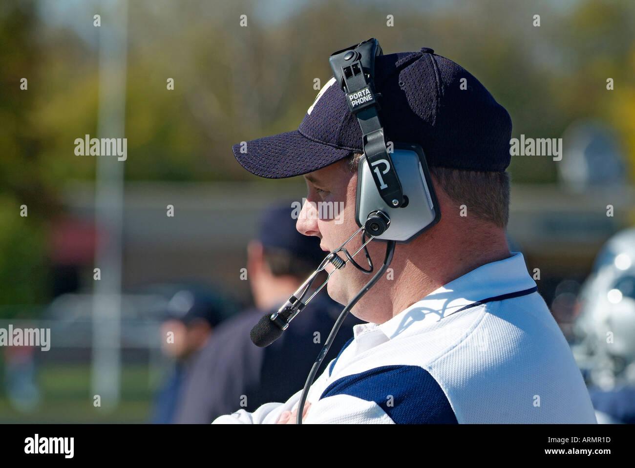 Entrenador de Fútbol americano a nivel High School comunicarse con otros entrenadores por medio del uso de auriculares inalámbricos Imagen De Stock