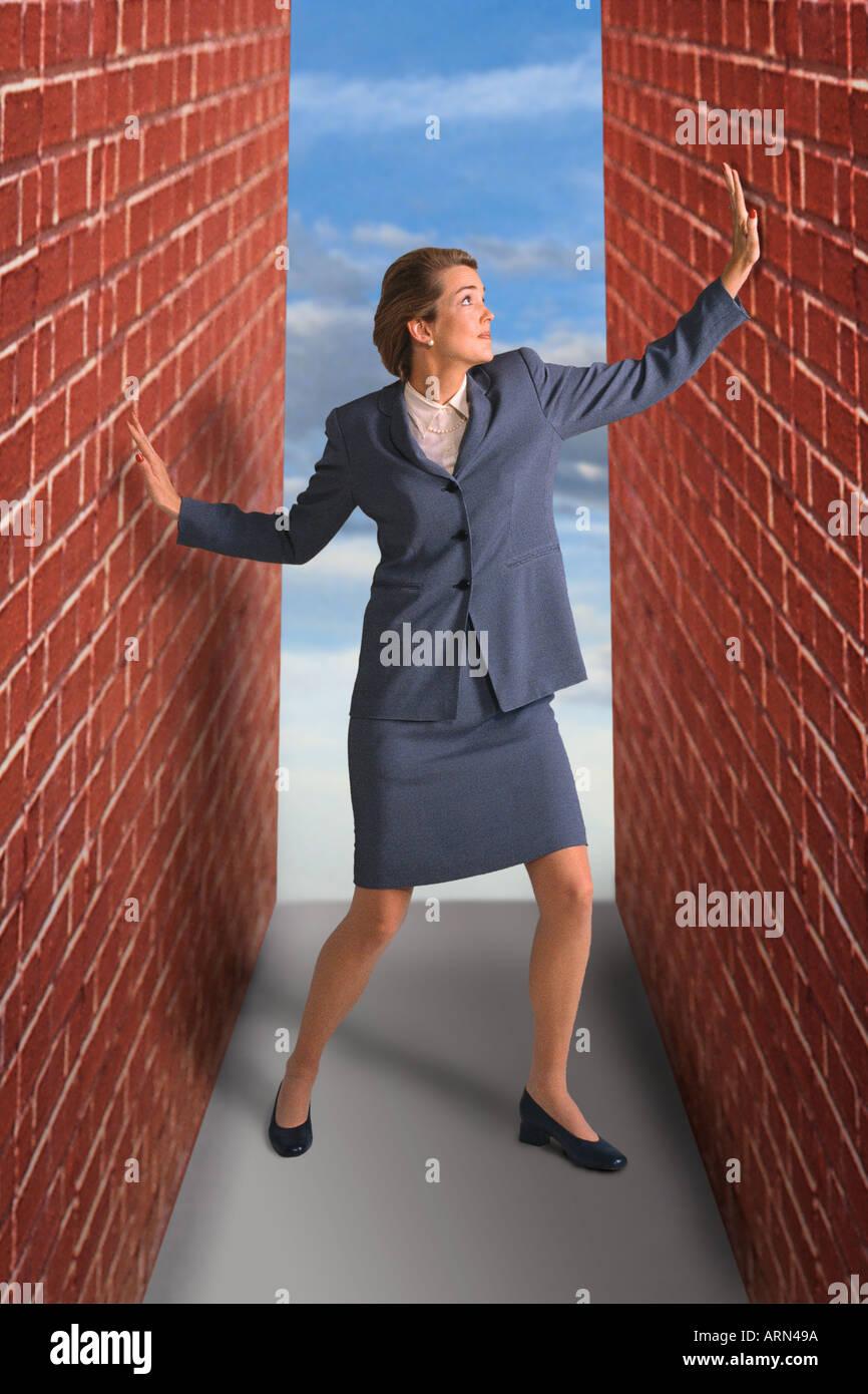 Mujer atrapada entre las paredes de ladrillo Foto de stock