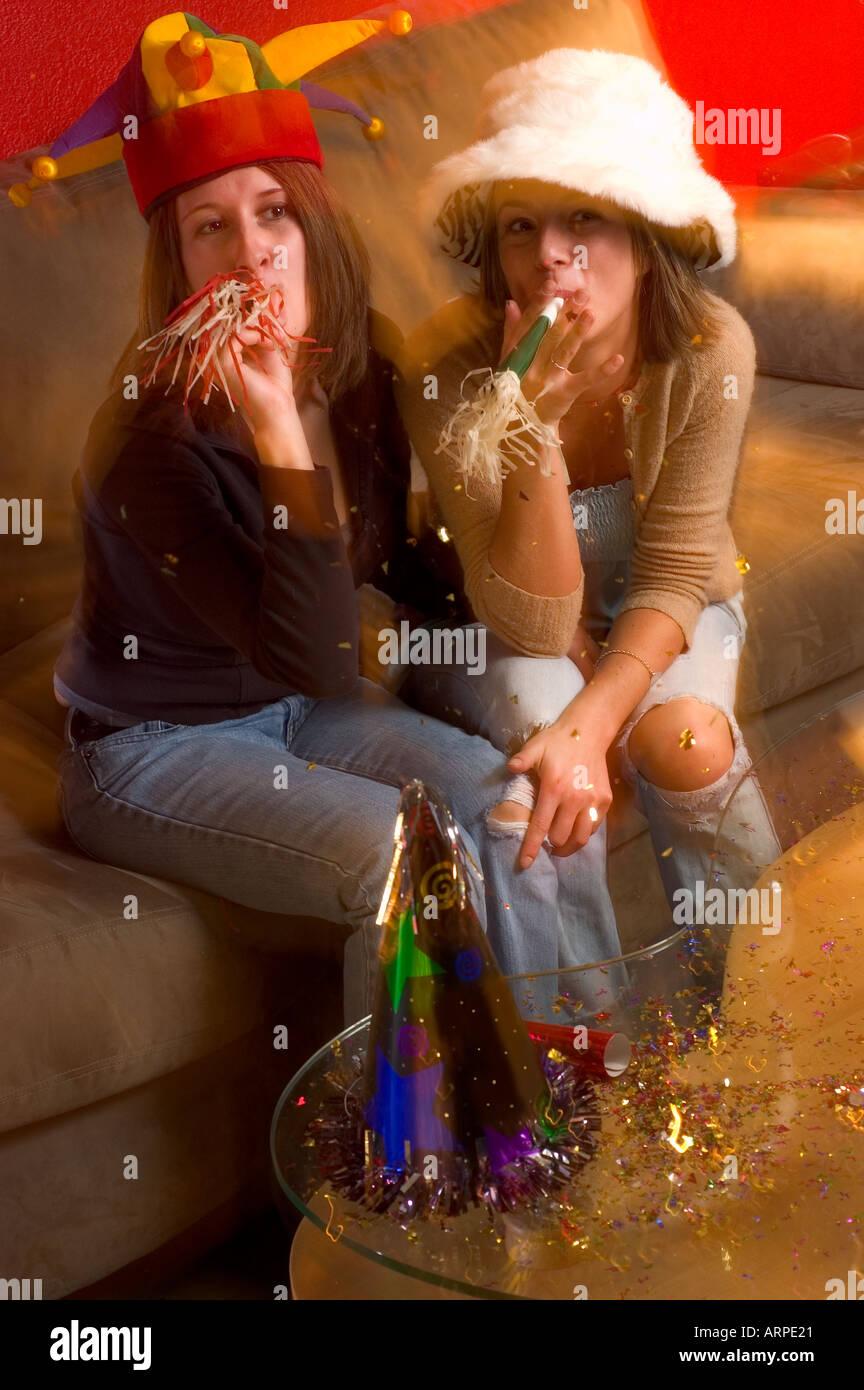 Dos mujeres jóvenes en una fiesta de Año Nuevo portando sombreros divertidos  con matracas u otros objetos para hacer ruido. a07dfb4d7e7