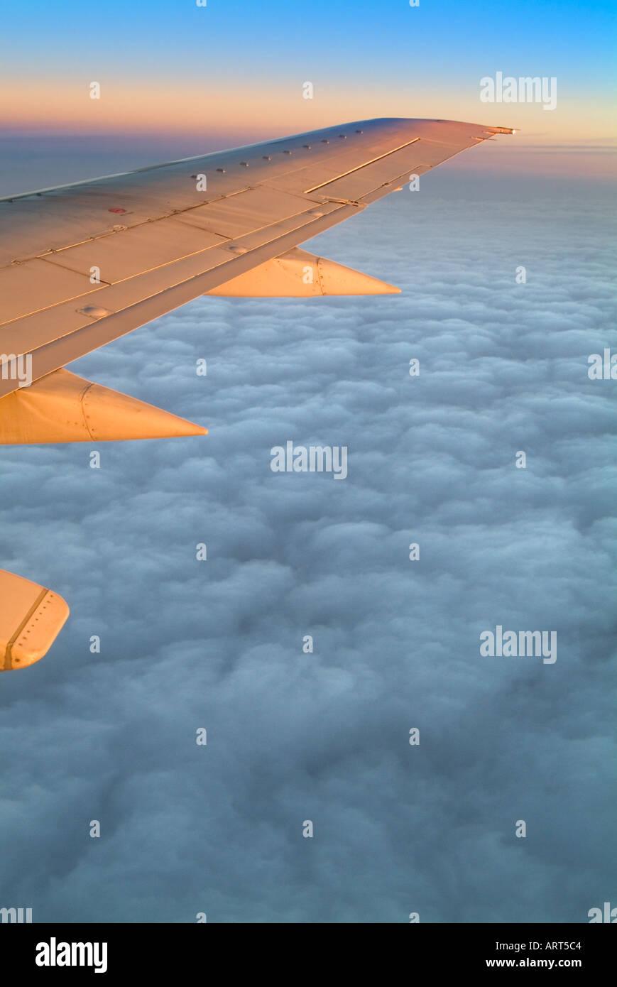 Ala de avión jet volando por encima de las nubes a Sunise Foto de stock