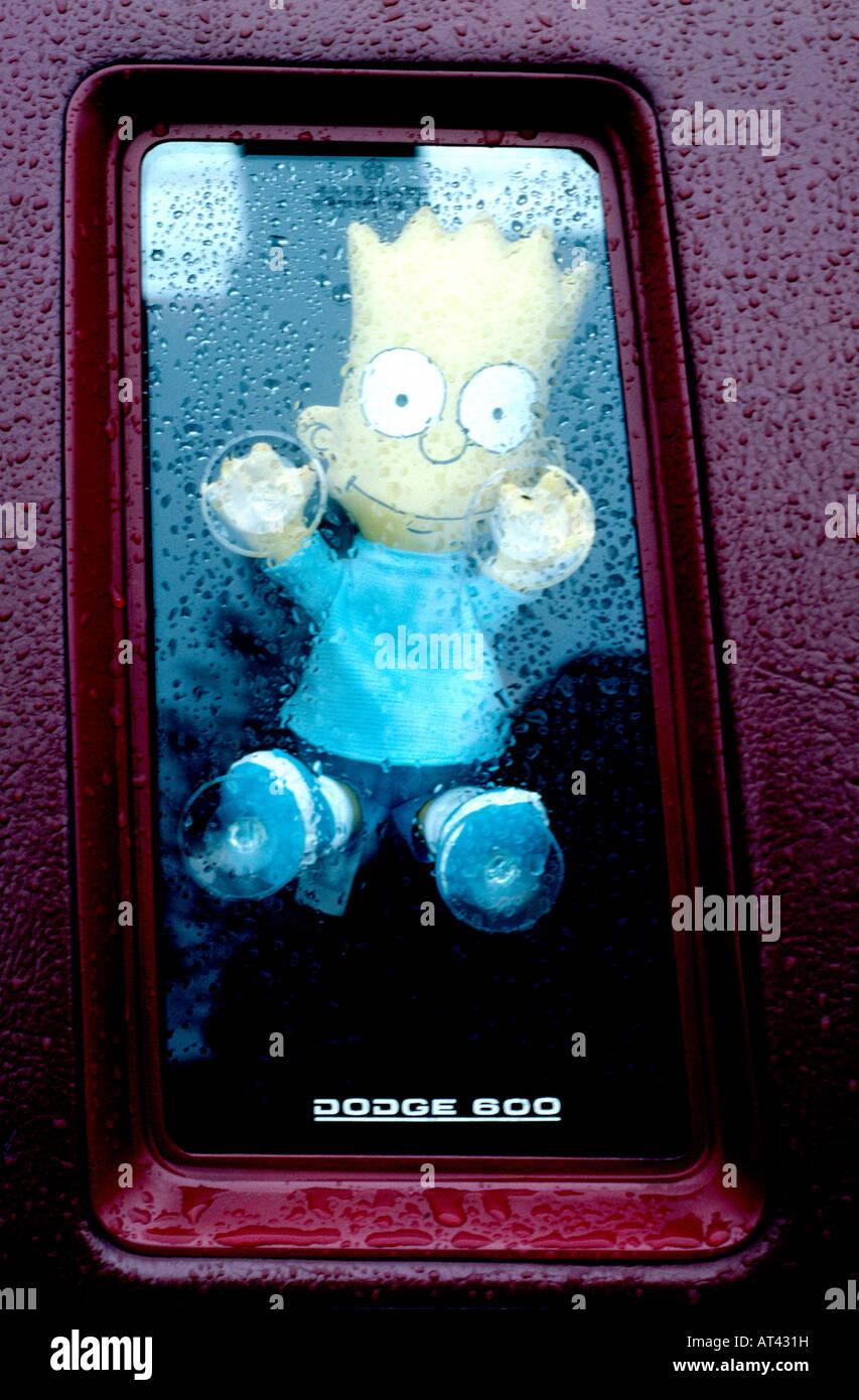 Kitsch Bart Simpson toy atascado en el interior del coche usa la ventana lateral Foto de stock