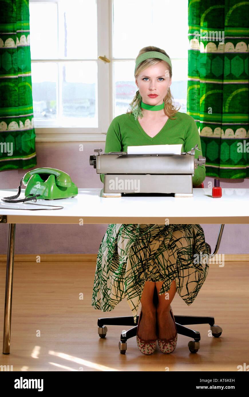 Mujer joven sentado en el escritorio Imagen De Stock