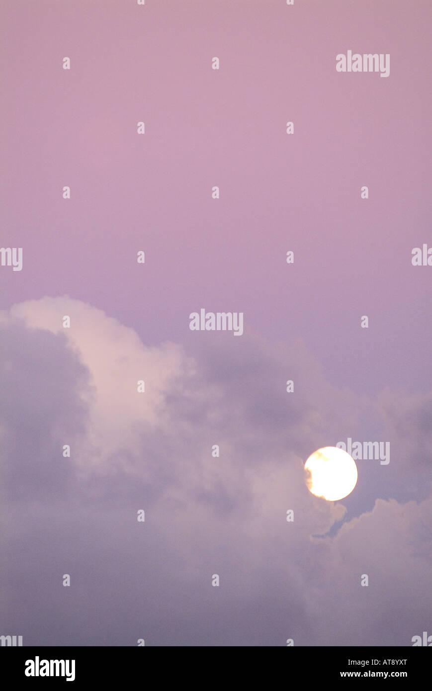 La luz de la luna llena en un cielo con lavanda hinchadas nubes blandas Foto de stock