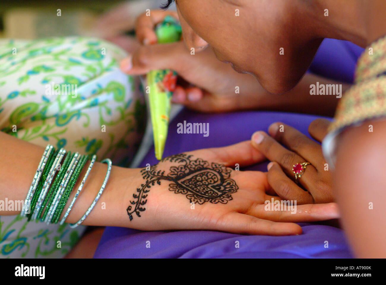 La mujer que recibe un diseño de henna mendhi en el interior de la palma de su mano en preparación para su ceremonia de boda hindi Foto de stock