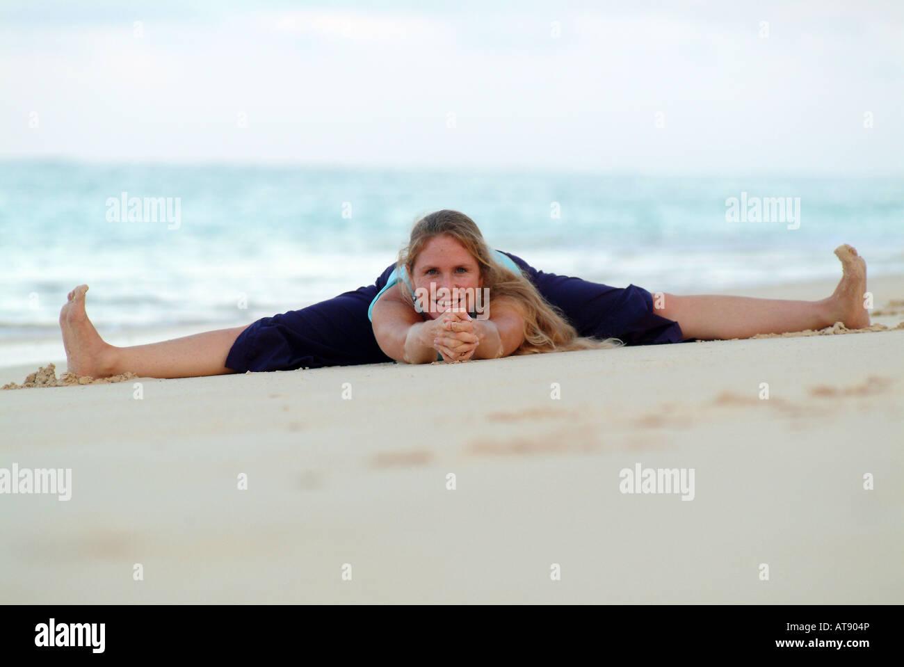 Mujer en el yoga se divide el estiramiento en la playa de arena blanca, Hawai Foto de stock