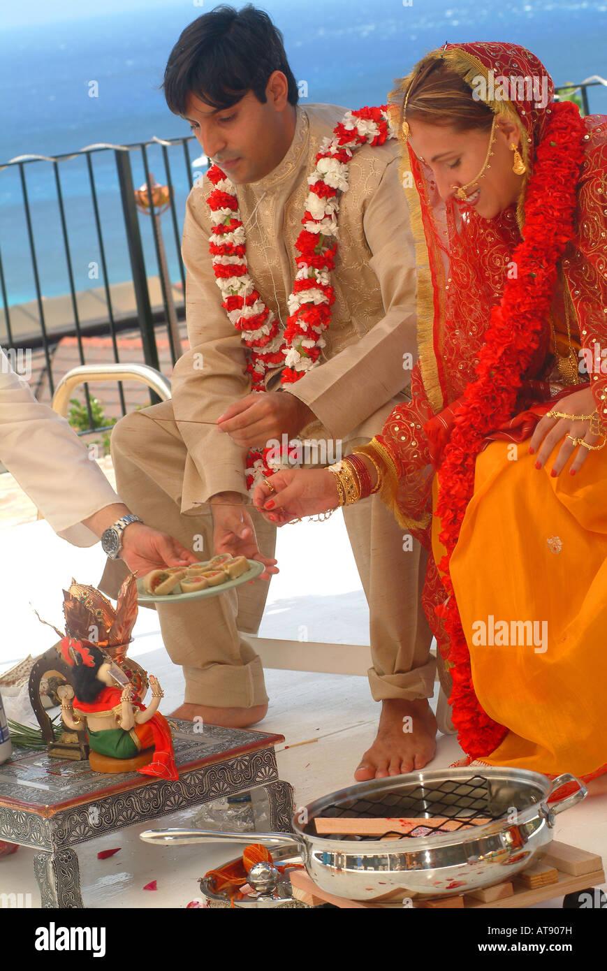 Hindi Tradditional boda con el novio vestidos de novia y flores de clavel con adornos indios Foto de stock