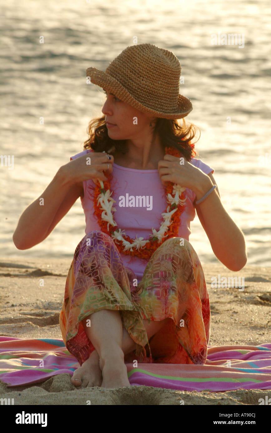 Mujer de principios thirtys de vacaciones en Hawaii, en la playa vistiendo flor leis y un sombrero cerca del atardecer Foto de stock