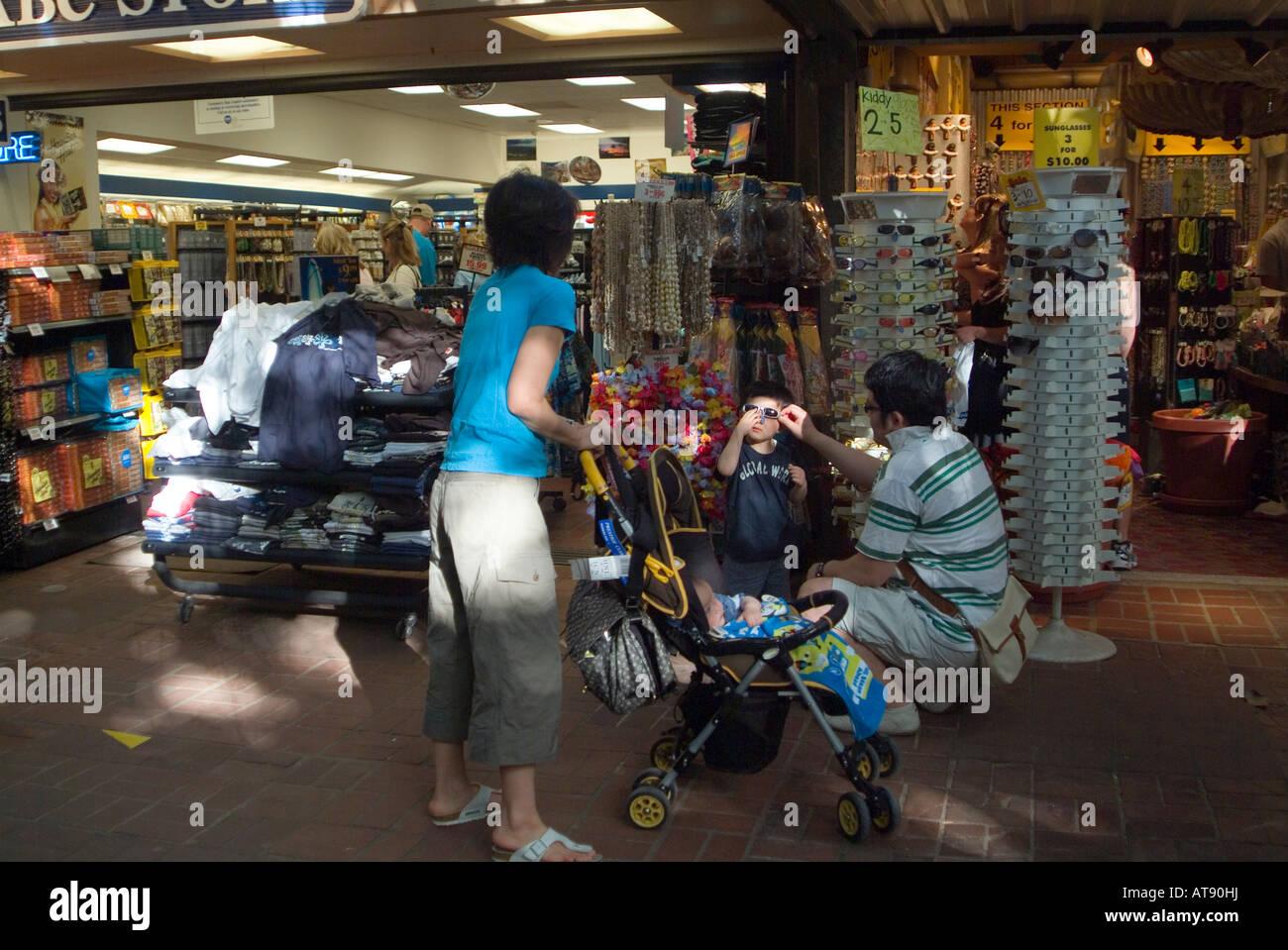 Los turistas de pie en frente de las tiendas en el mercado internacional en Waikiki. Foto de stock