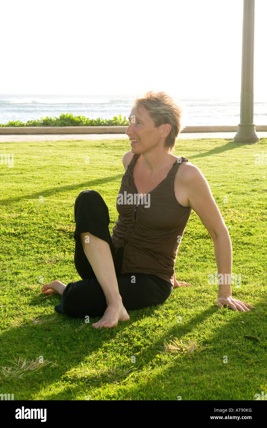Una mujer prácticas yoga en la hierba en Queens Park, en la playa de Waikiki. Foto de stock