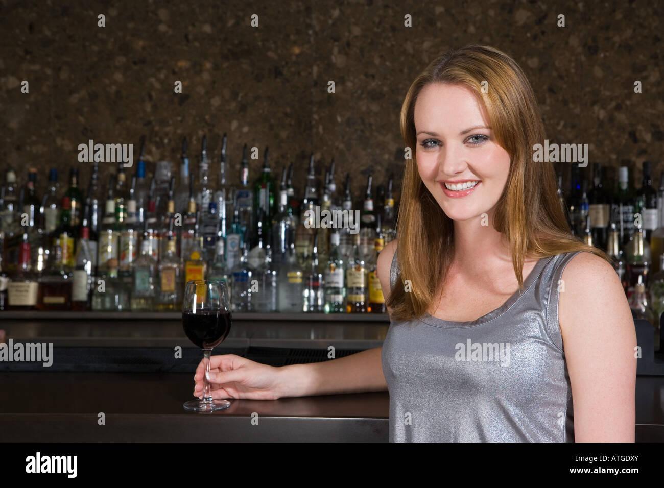 Mujer sonriente bebiendo vino en un bar. Foto de stock