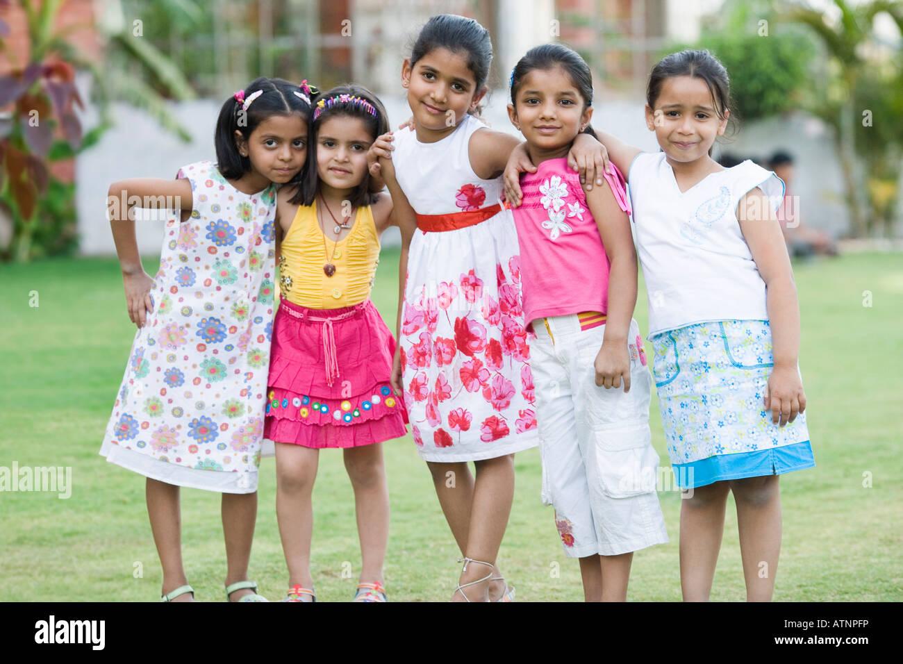 Retrato de cinco niñas de pie en un césped Imagen De Stock