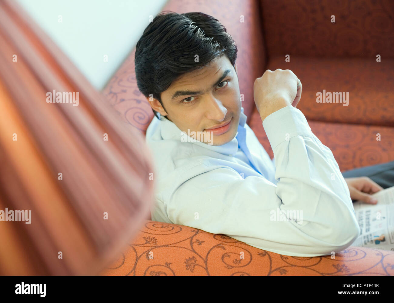 Retrato de un joven sentado en un sofá y la celebración de un periódico Imagen De Stock