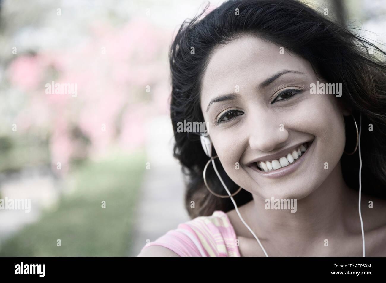 Retrato de una joven mujer escuchando música y sonriendo Imagen De Stock