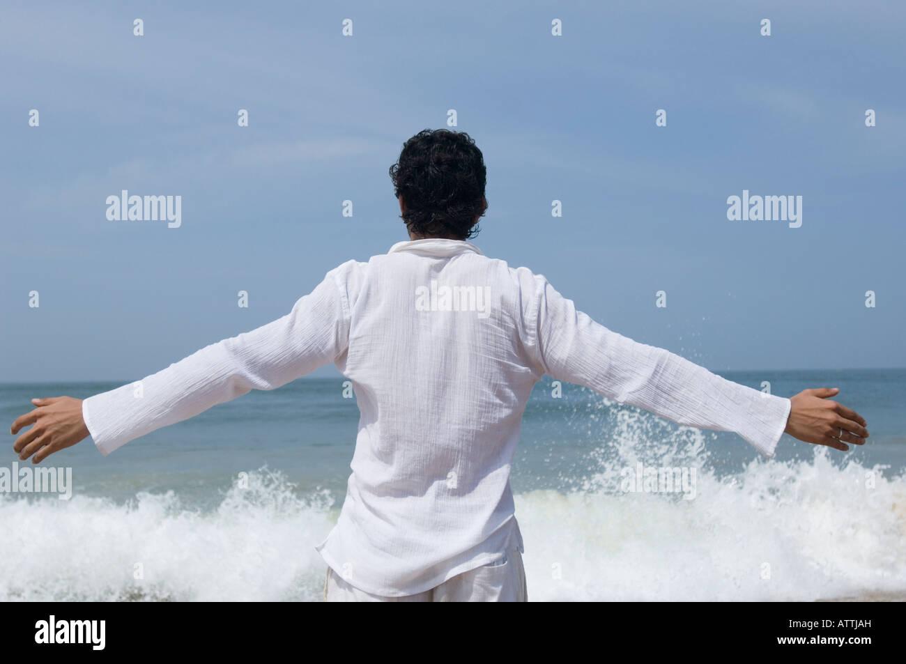 Vista posterior de un hombre joven de pie en la playa Imagen De Stock