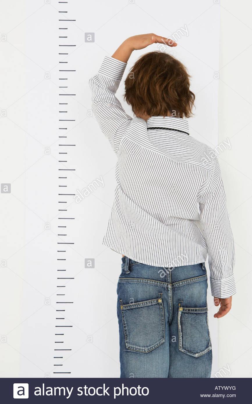 Chico adentro midiendo su altura en una pared. Imagen De Stock