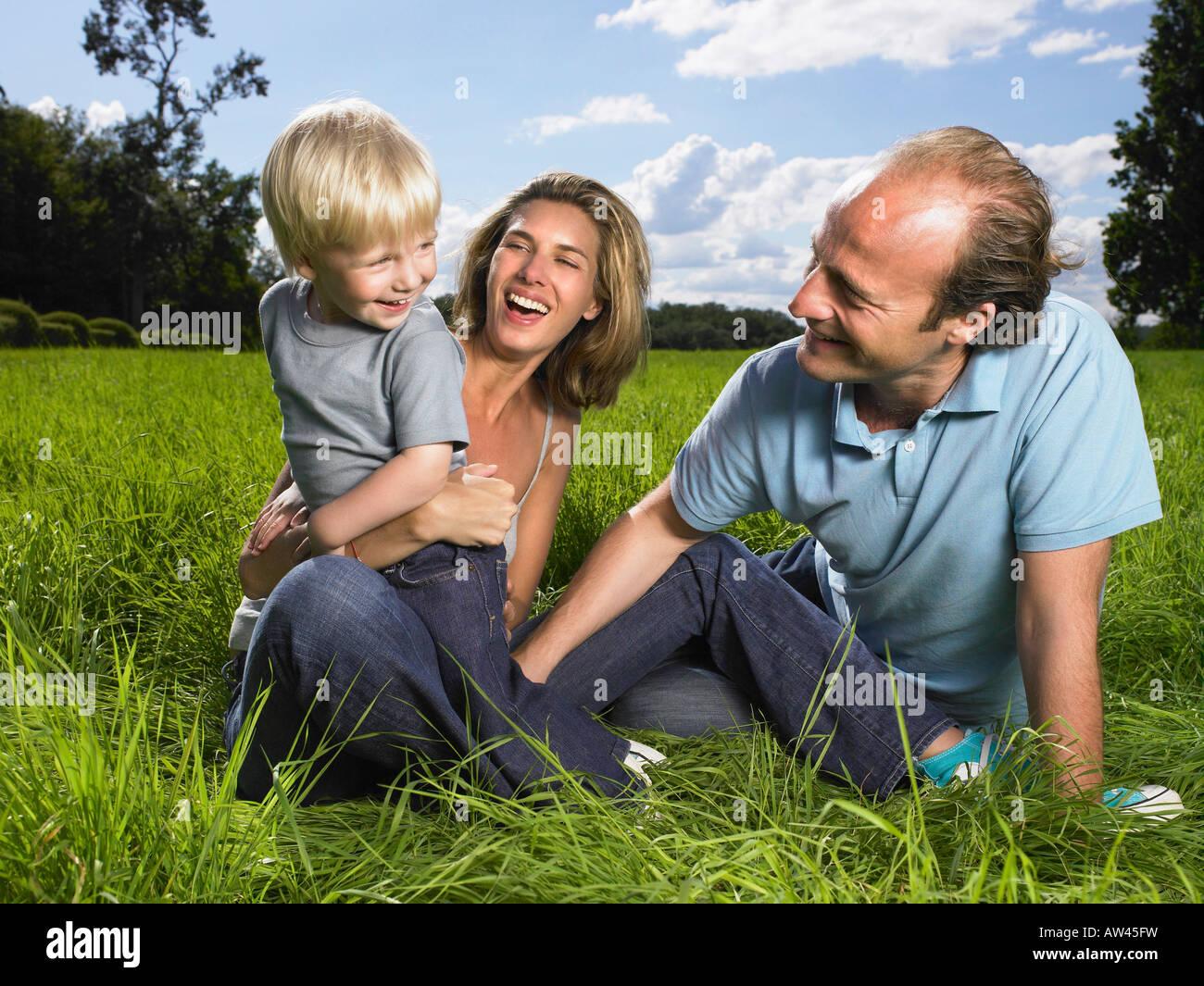 Familia disfrutando de un buen momento en un campo. Imagen De Stock