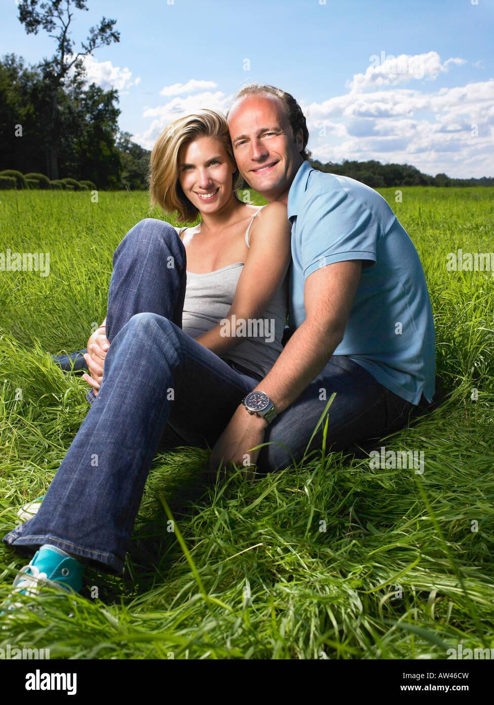 Pareja sentada en un campo. Imagen De Stock