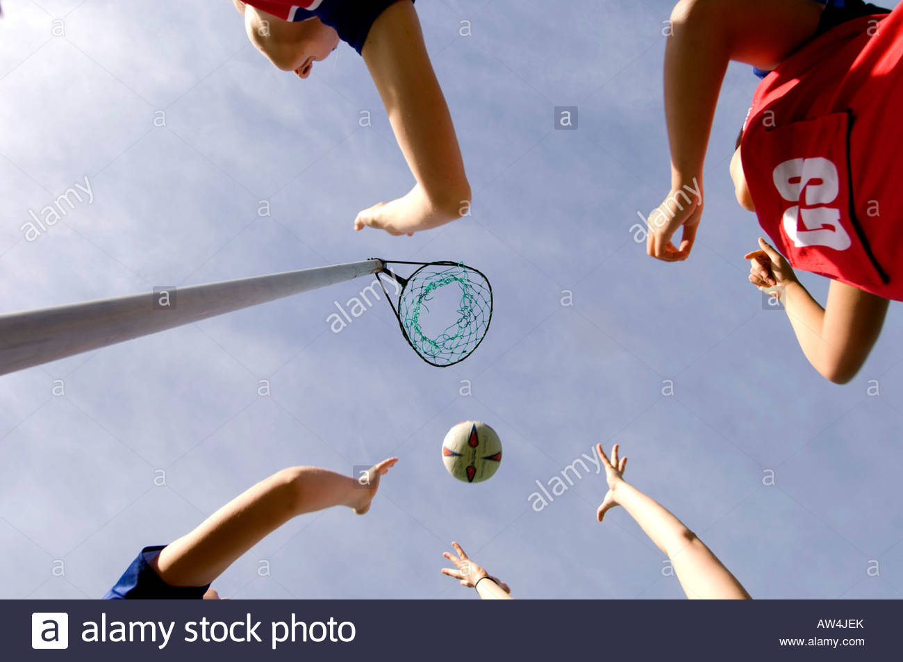 Mujer jugando baloncesto con balón y net contra un cielo azul Imagen De Stock