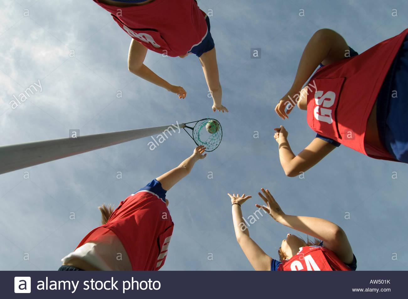 Señoras jugando baloncesto con balón y net contra un cielo azul Imagen De Stock