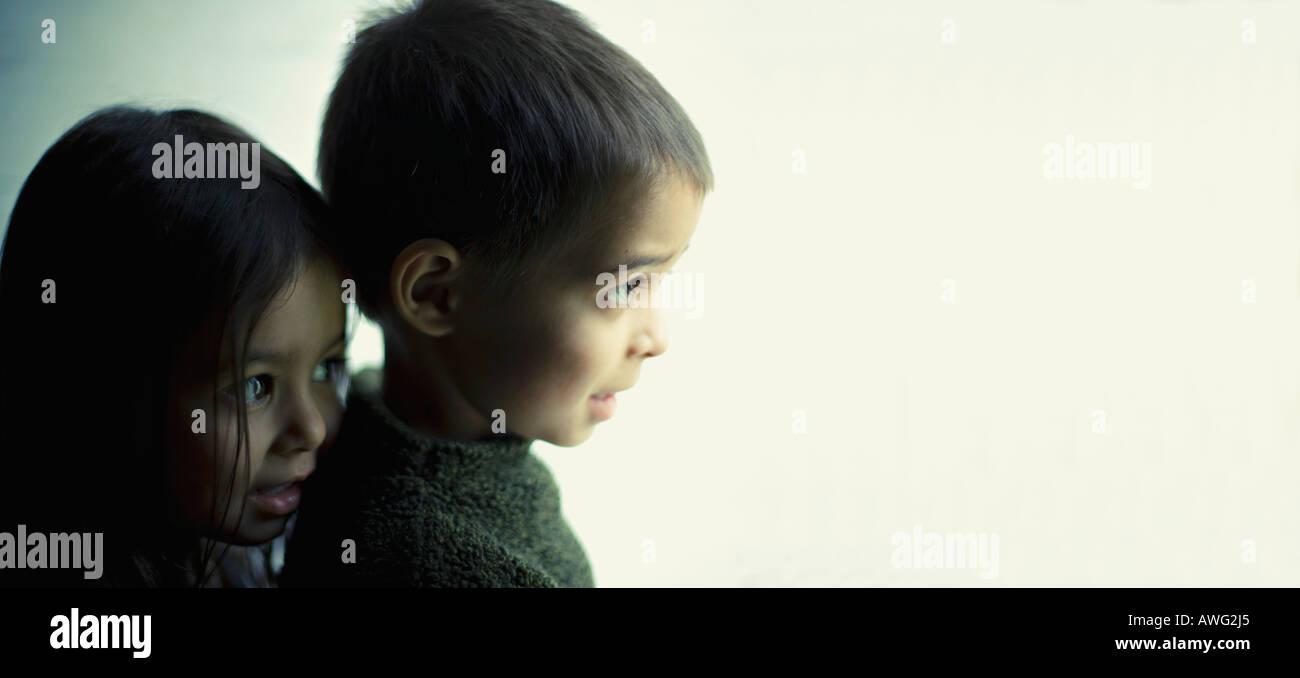 Gran Hermano y hermana pequeña mirar hacia fuera por la puerta Imagen De Stock