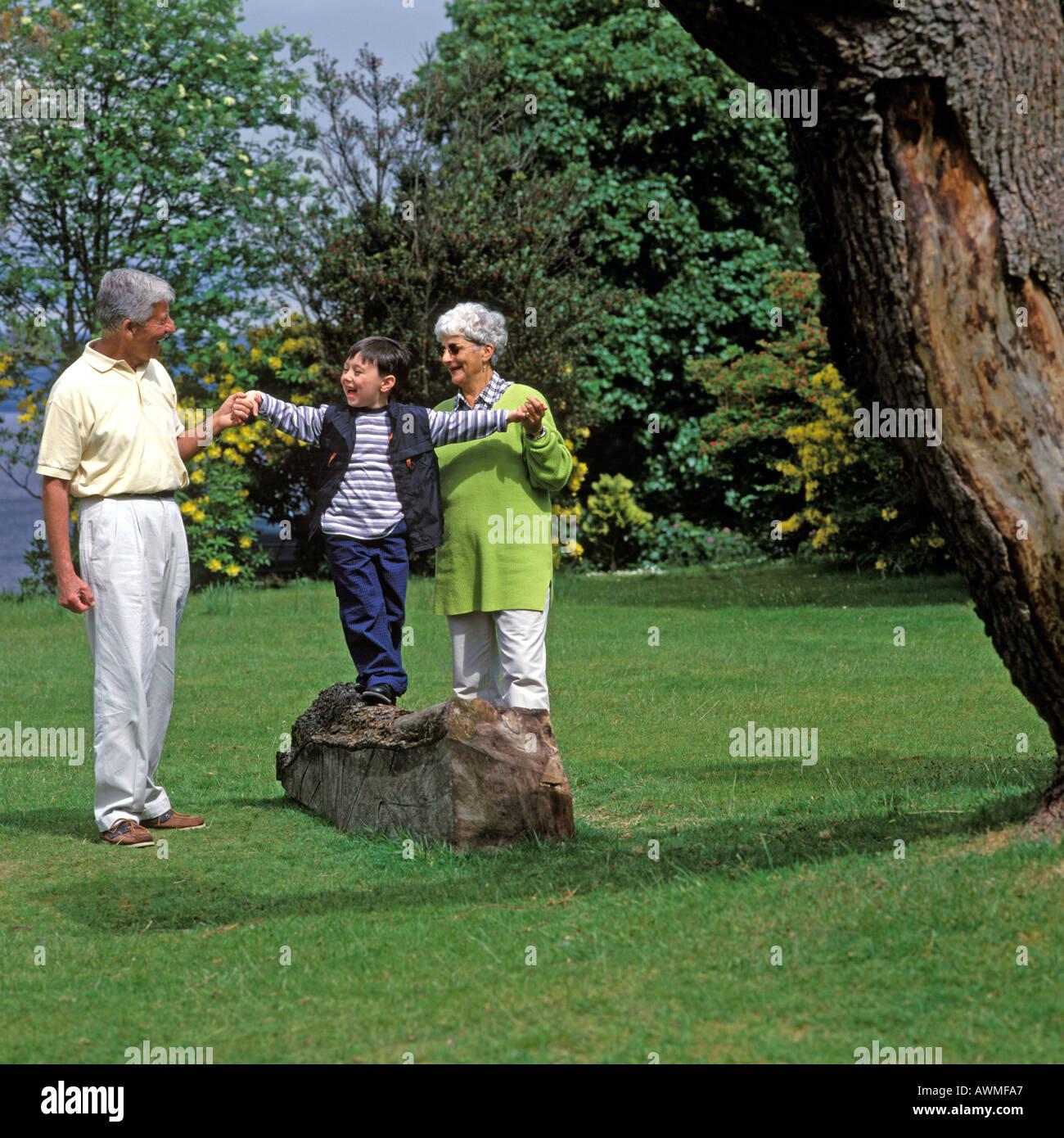 Los abuelos CON EL NIÑO EN EL PARQUE Foto de stock