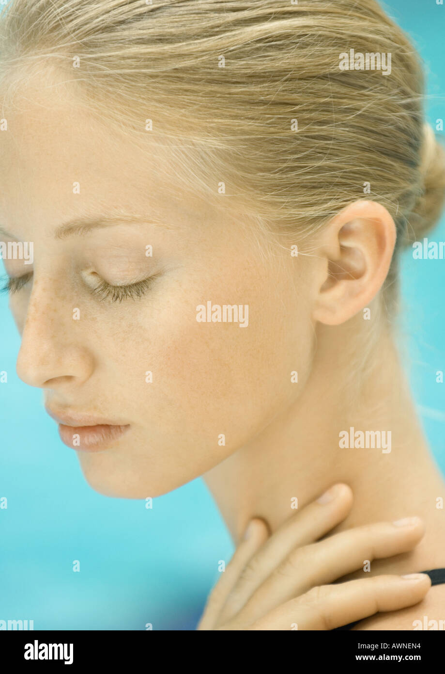Mujer con la mano en el cuello, piscina en segundo plano. Imagen De Stock