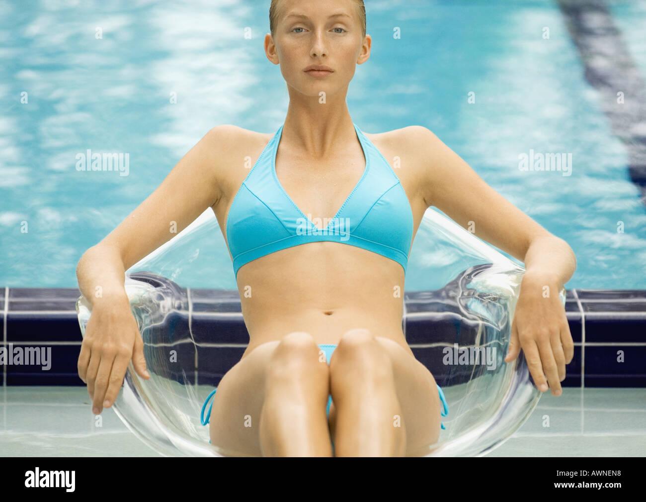 Mujer en bikini sentada en la silla transparente por la piscina Foto de stock