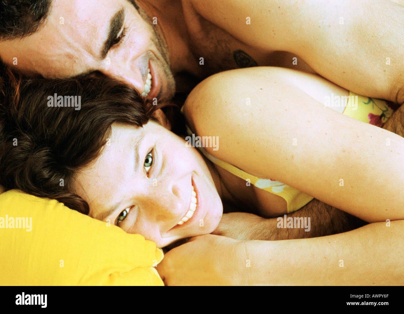 Pareja en la cama, el hombre acostado sobre la espalda, cerca de la mujer. Foto de stock