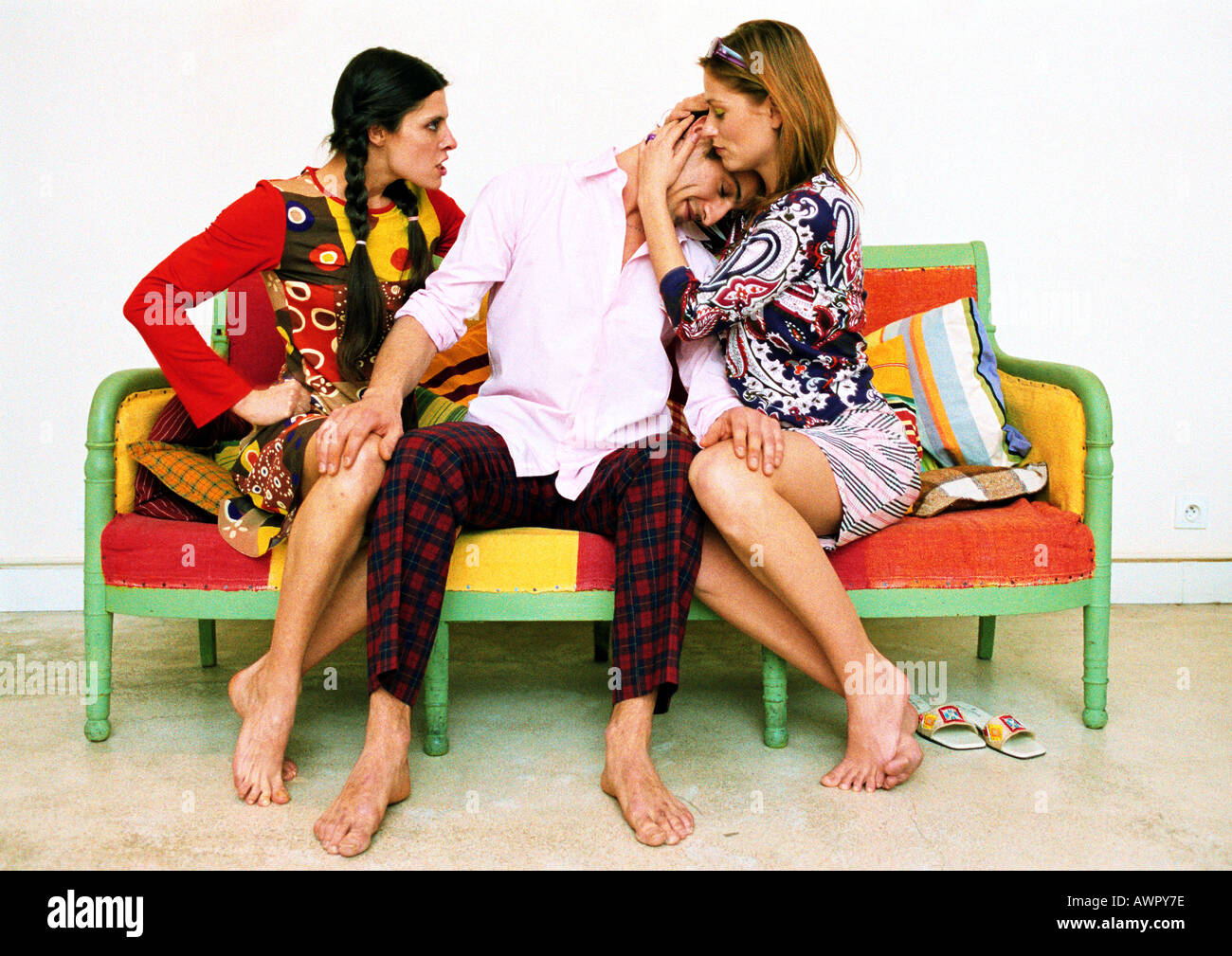 Dos mujeres y hombre en el sofá, el hombre la cabeza apoyada en el hombro de una mujer, otra mujer infeliz. Foto de stock
