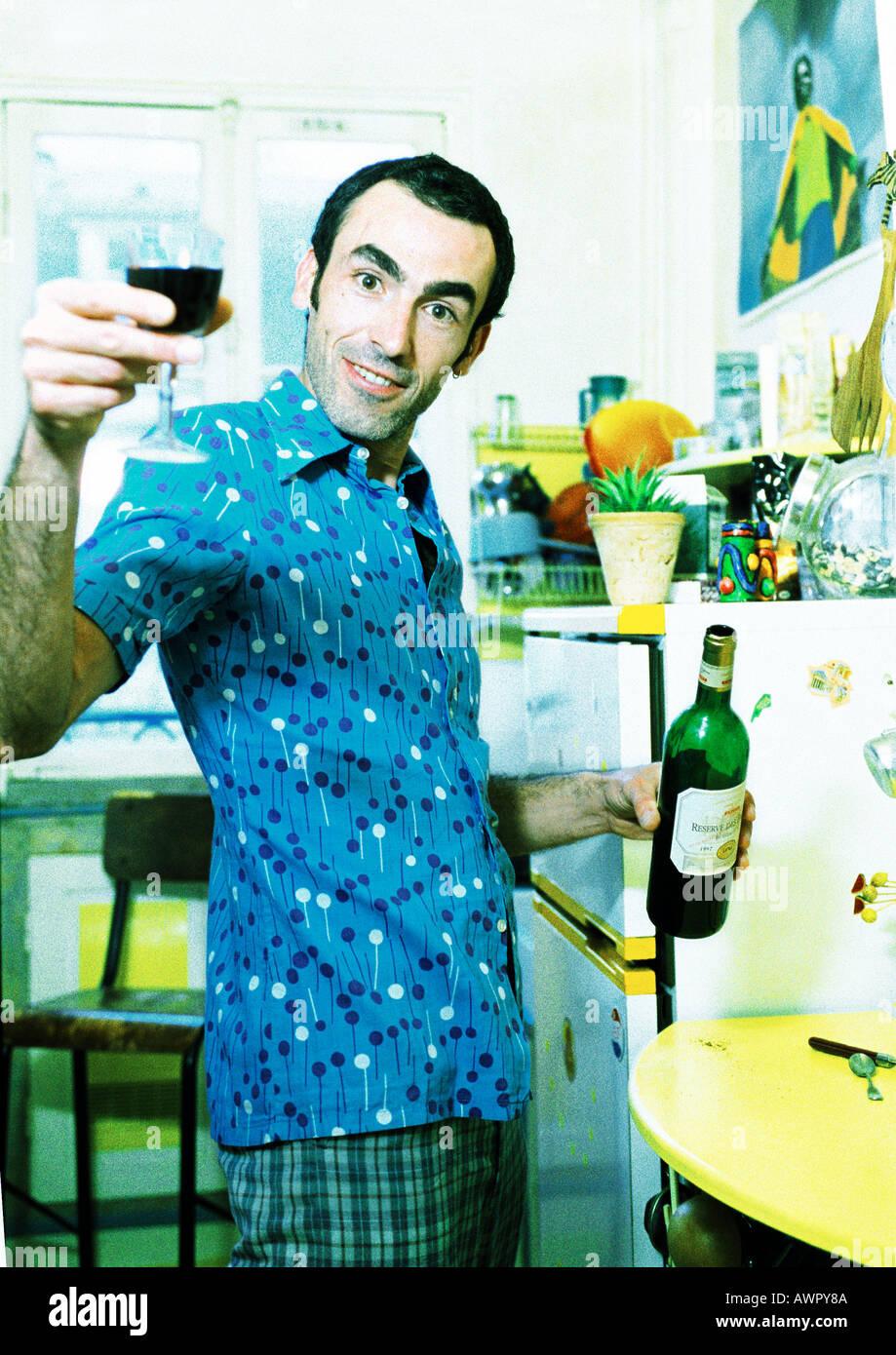 El hombre en la cocina sosteniendo una botella de vino, levantando su copa, retrato. Foto de stock