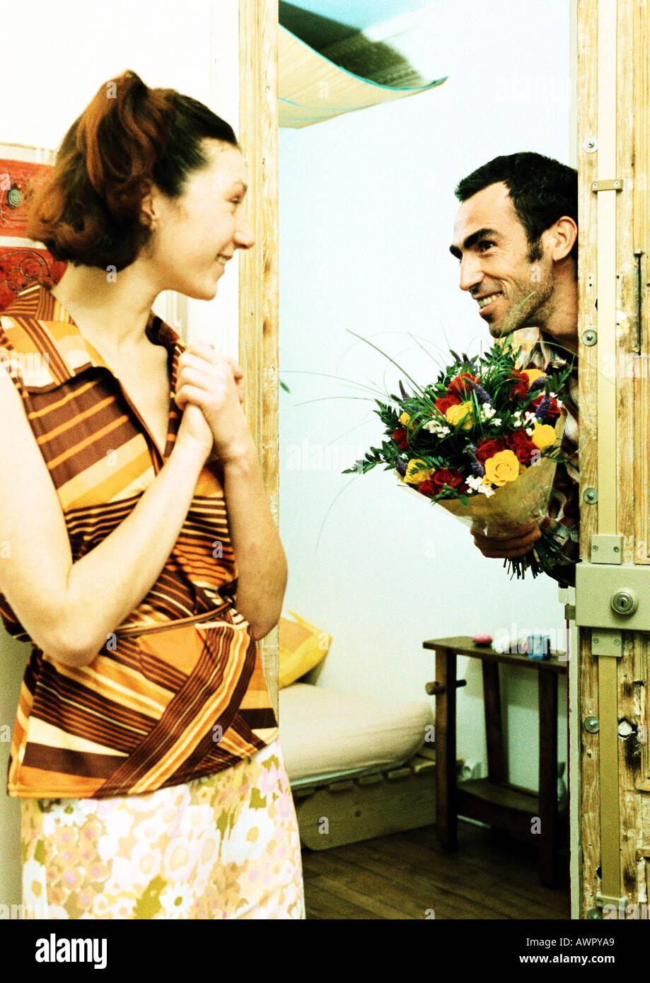 Pareja, hombre caminando a través de la puerta sosteniendo bouquet de flores, mujer sonriendo. Foto de stock