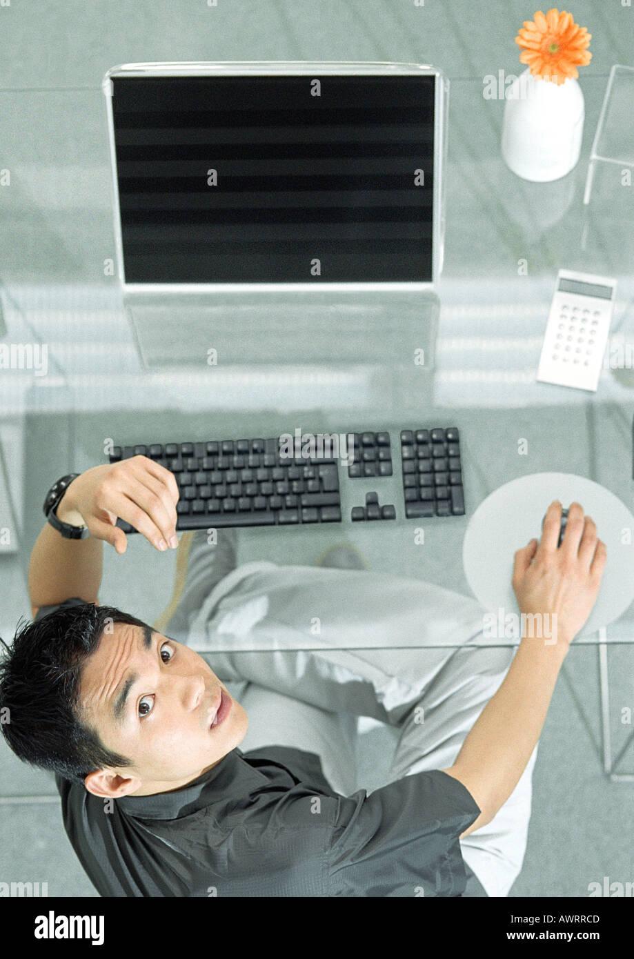 Hombre y escritorio con dispositivos futurista, un alto ángulo de visualización, Retrato Foto de stock