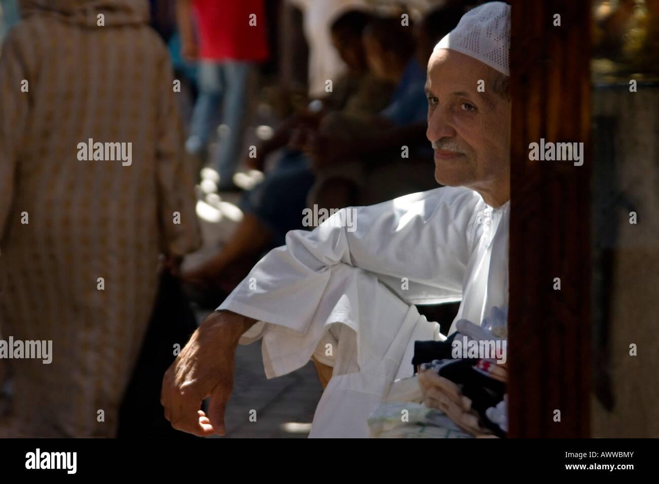 0a713214e838d Vertical horizontal de un anciano musulmán varón tendero de un blanco  inmaculado kaftan sentado fuera Imagen