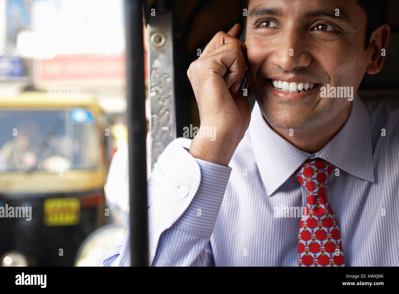 Hombre de negocios mediante teléfono móvil, sonriendo Imagen De Stock