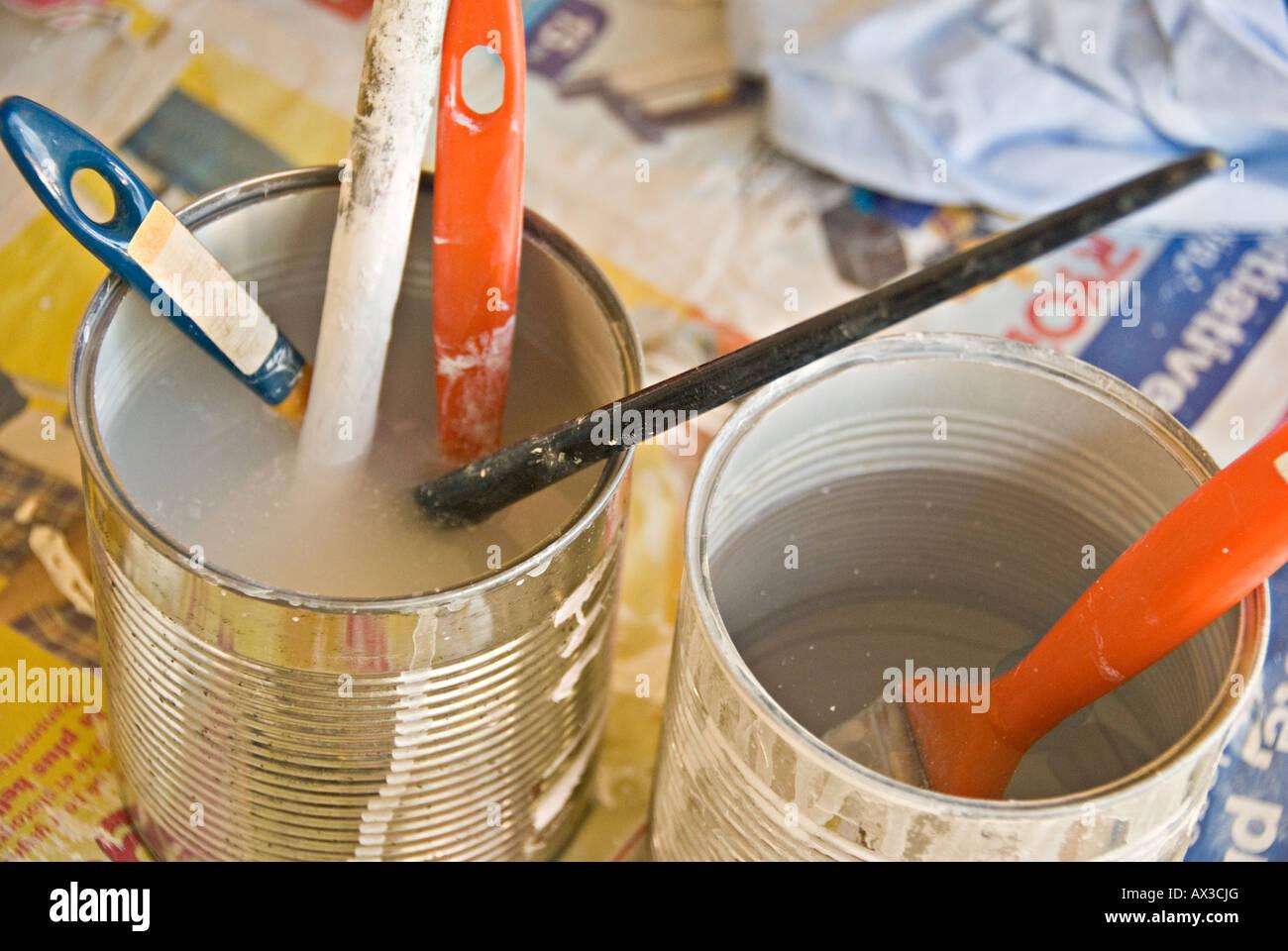 Pinceles empapar en latas de agua Imagen De Stock
