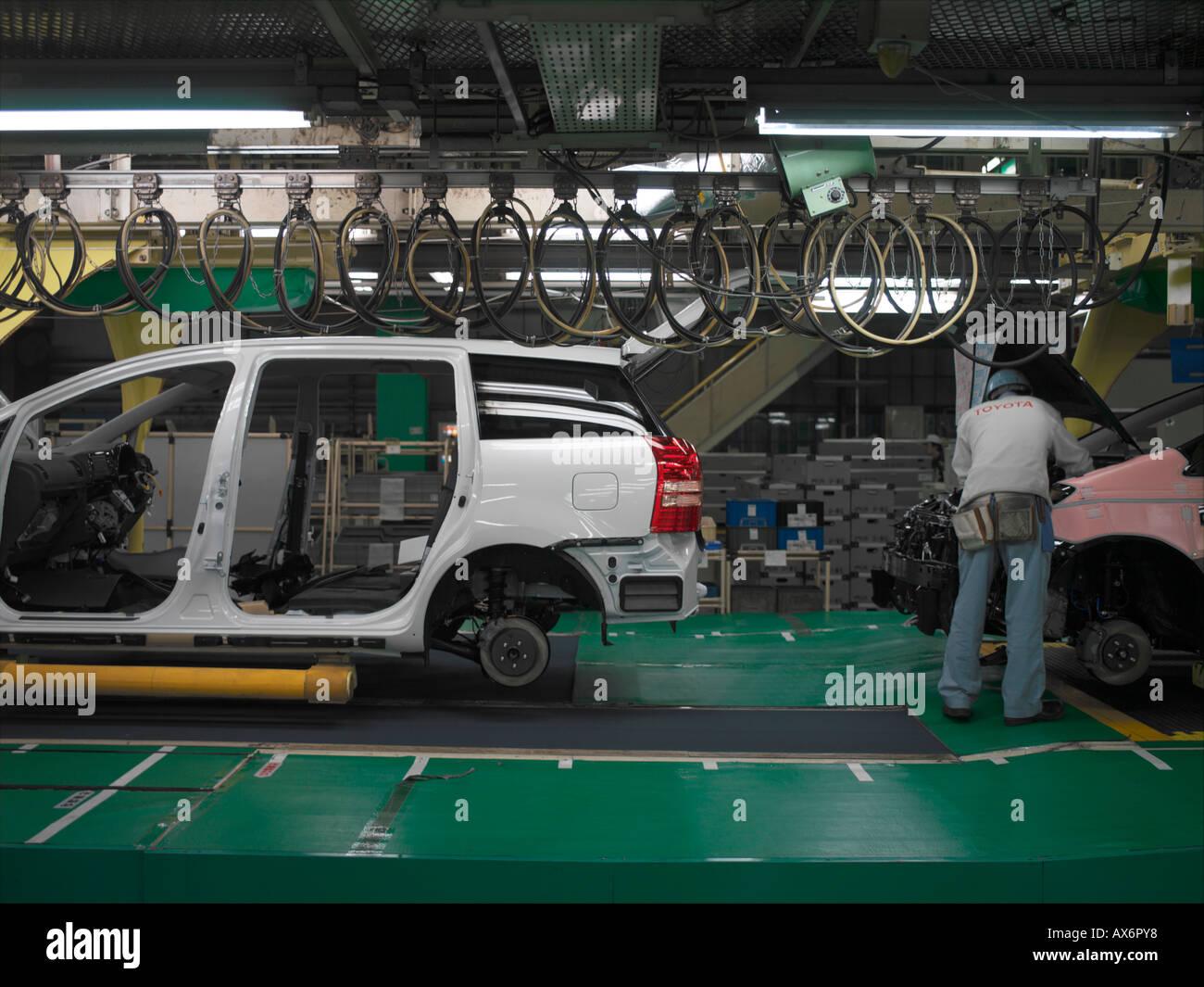 Trabajadores de la fábrica produciendo el Toyota Prius híbrido de coches trabajan en la línea de ensamblaje en la ciudad de Toyota Imagen De Stock