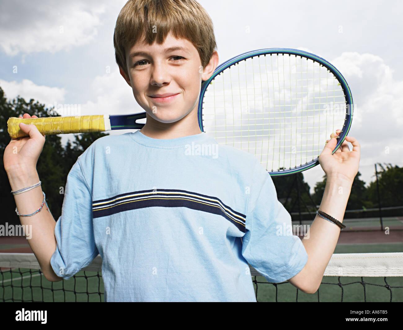 Niño sosteniendo raqueta de tenis Foto de stock
