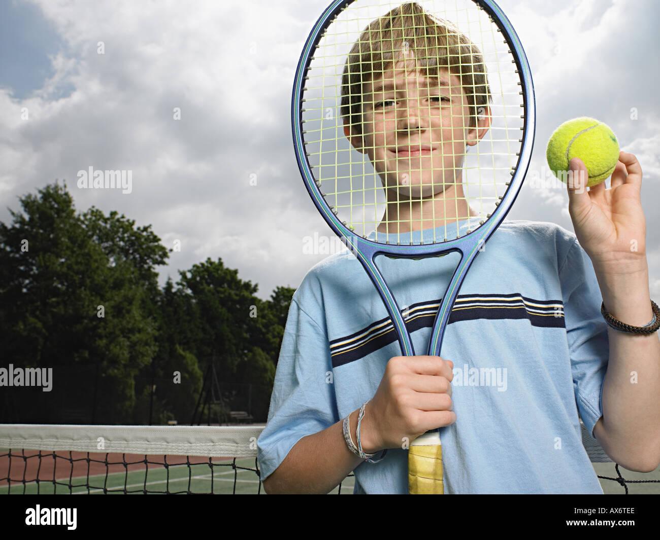 Niño sosteniendo la bola y la raqueta de tenis Foto de stock