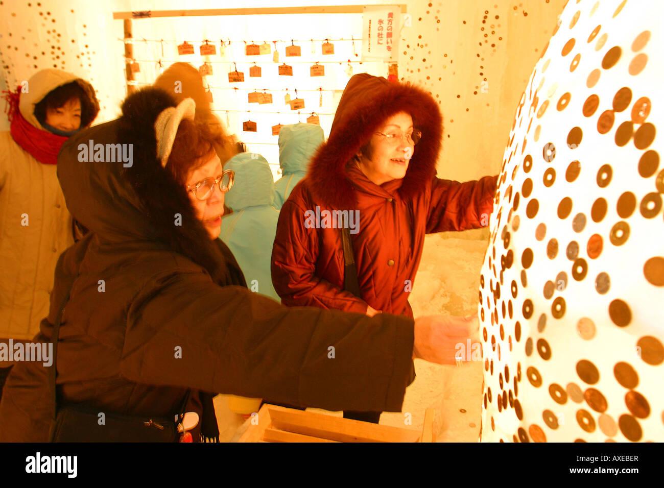 Poniendo las monedas en el hielo para la buena suerte en Sounkyo Festival de hielo Foto de stock