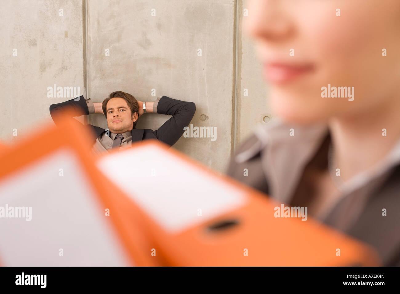 La empresaria llevando carpetas, empresario en el fondo Imagen De Stock