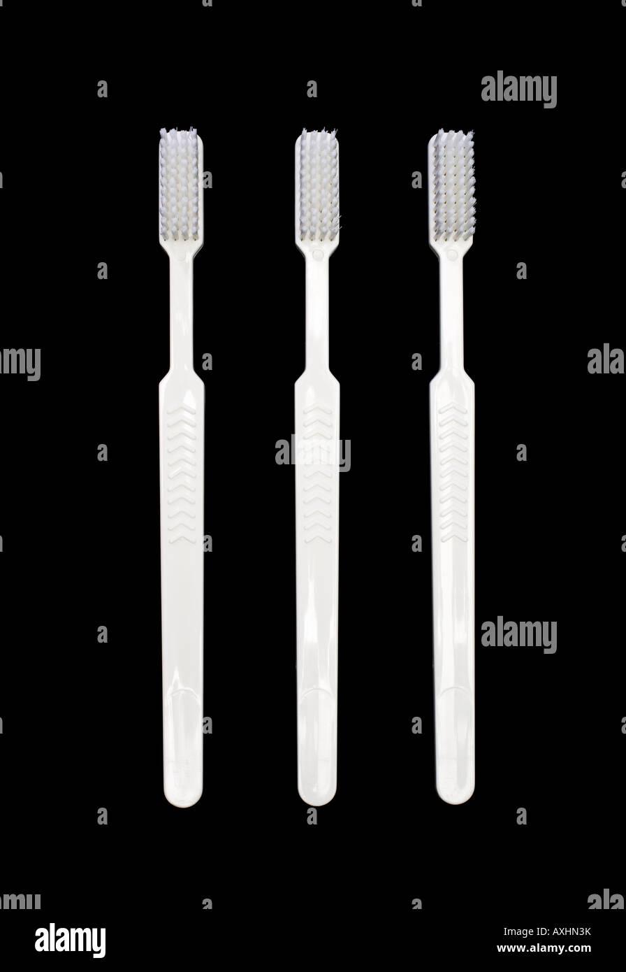 Tres cepillos de plástico blanco. Foto de stock