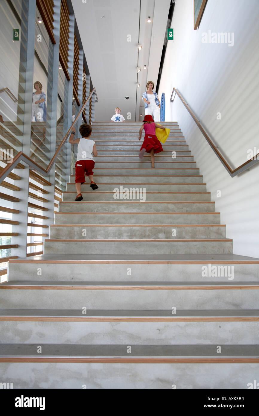 Niños corriendo hasta los pasos en el interior de la Galería de Arte Moderno de Brisbane, Queensland, Queensland Foto de stock