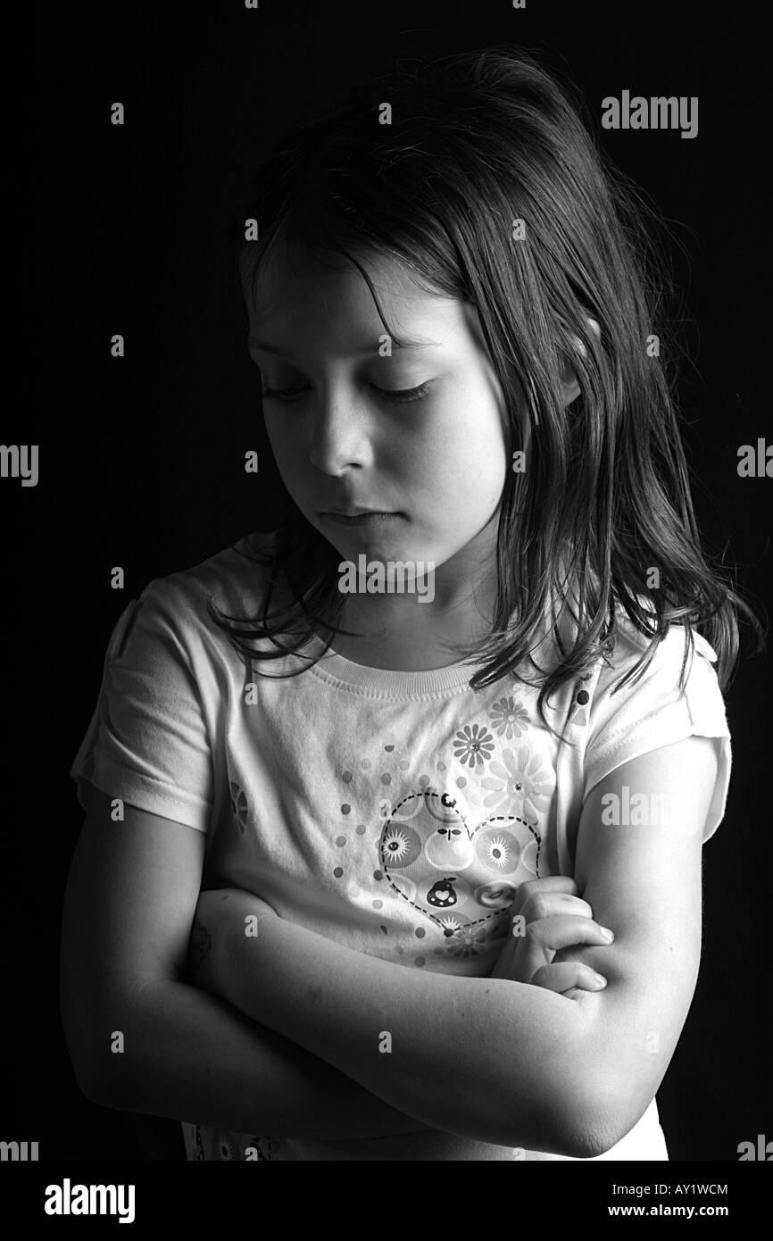 cff819317 Bonita foto de una niña de siete años mirando hacia abajo con los brazos  cruzados