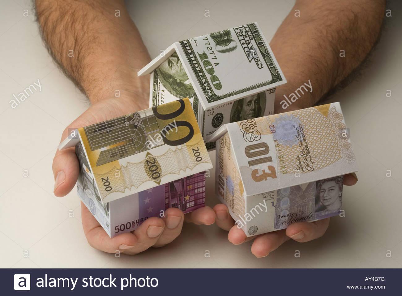 Hombre sujetando las casas hechas con el dólar, libra y billetes Foto de stock