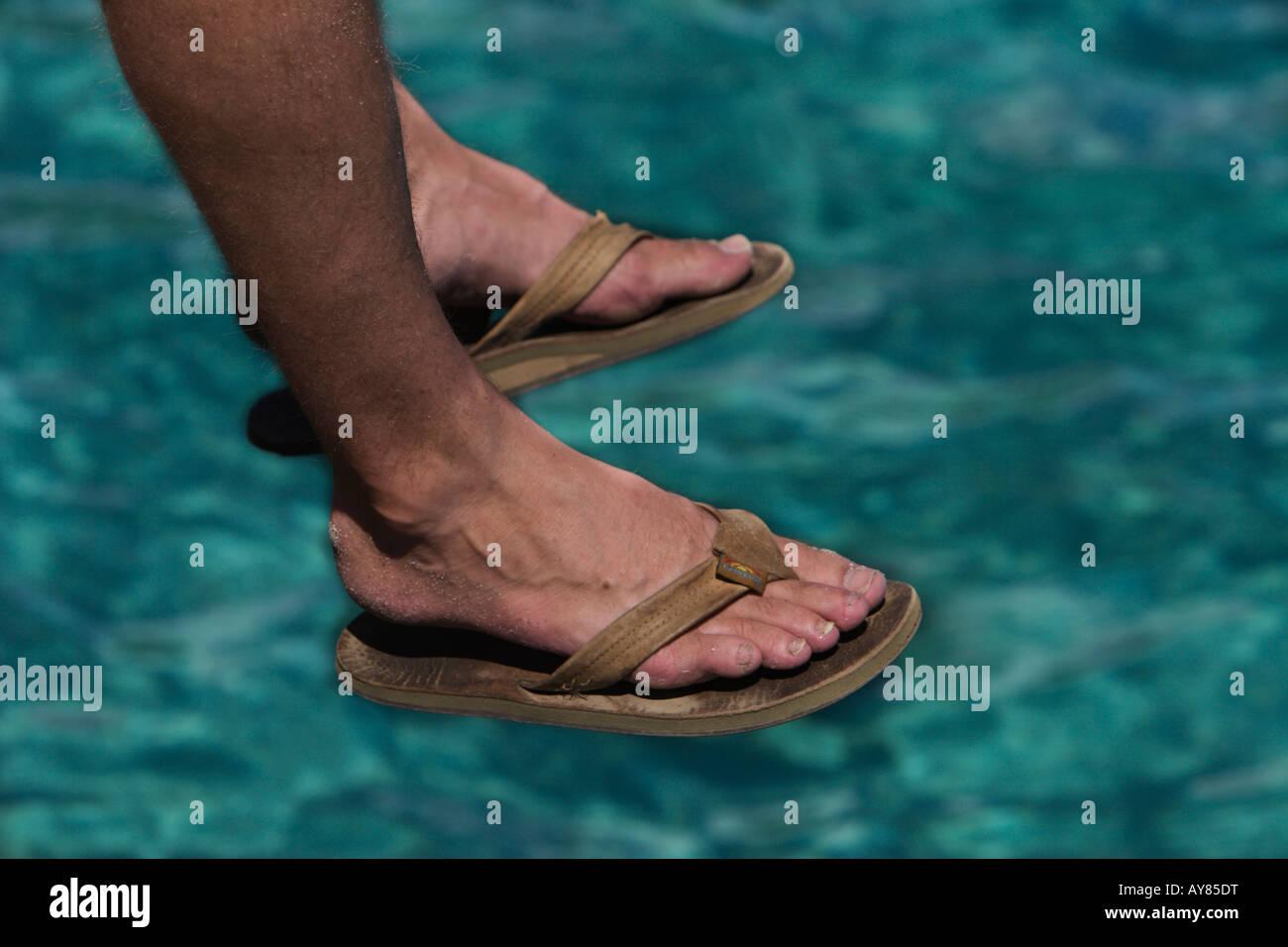 8acee4f3 Hombre de pie vistiendo chanclas (es decir, chanclas o sandalias) colgando  sobre el