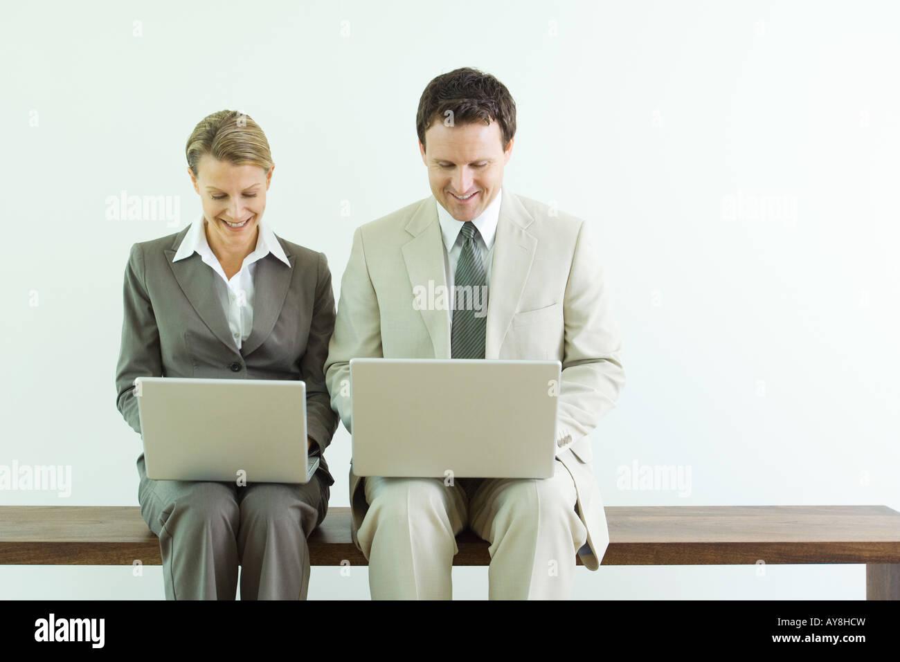 Asociados de negocios masculinos y femeninos sentados uno al lado del otro, ambos utilizando ordenadores portátiles Foto de stock