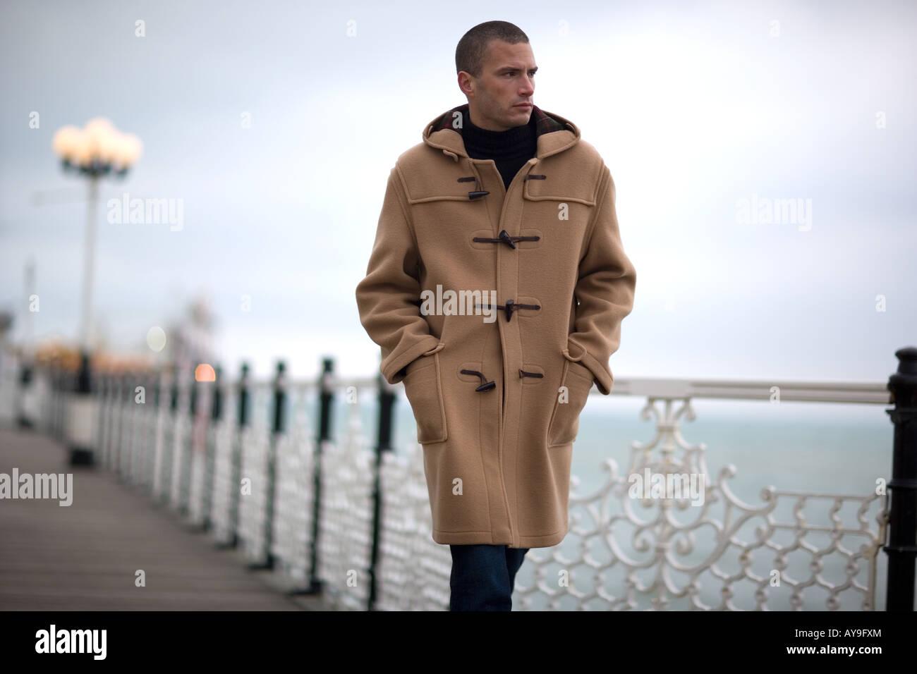 Hombre de duffle coat caminando por el muelle en Brighton, REINO UNIDO Imagen De Stock