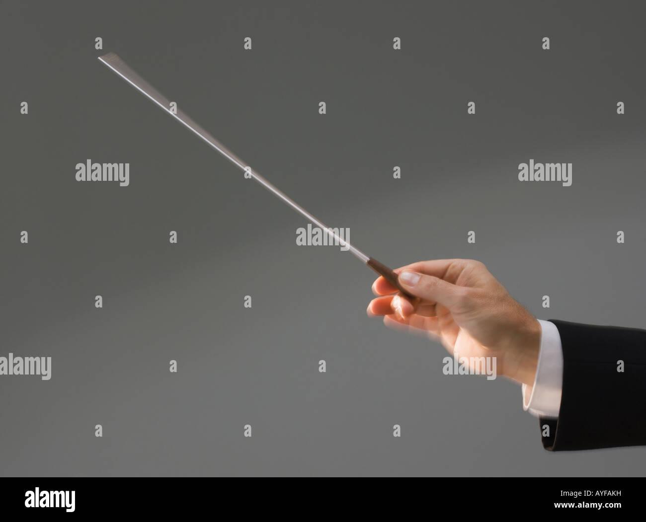La mano que sostiene el conductor masculino baton Foto de stock