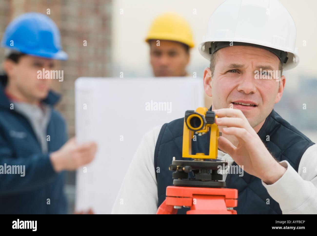 Agrimensor macho mirando a través del dispositivo de medición Imagen De Stock
