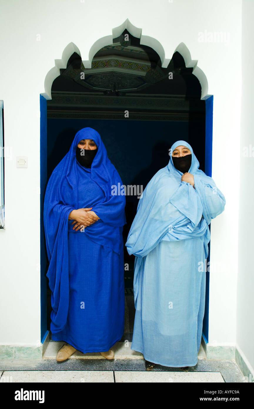 La mujer musulmana vestida con el tradicional chador o nikab está enmarcado por un umbral arqueado Marruecos Imagen De Stock